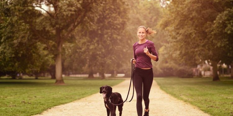 lady running in a park with dog